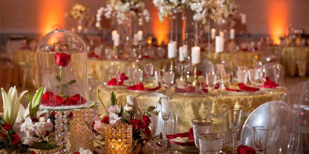 Landscape view of a rosy red and gold themed wedding reception decor.