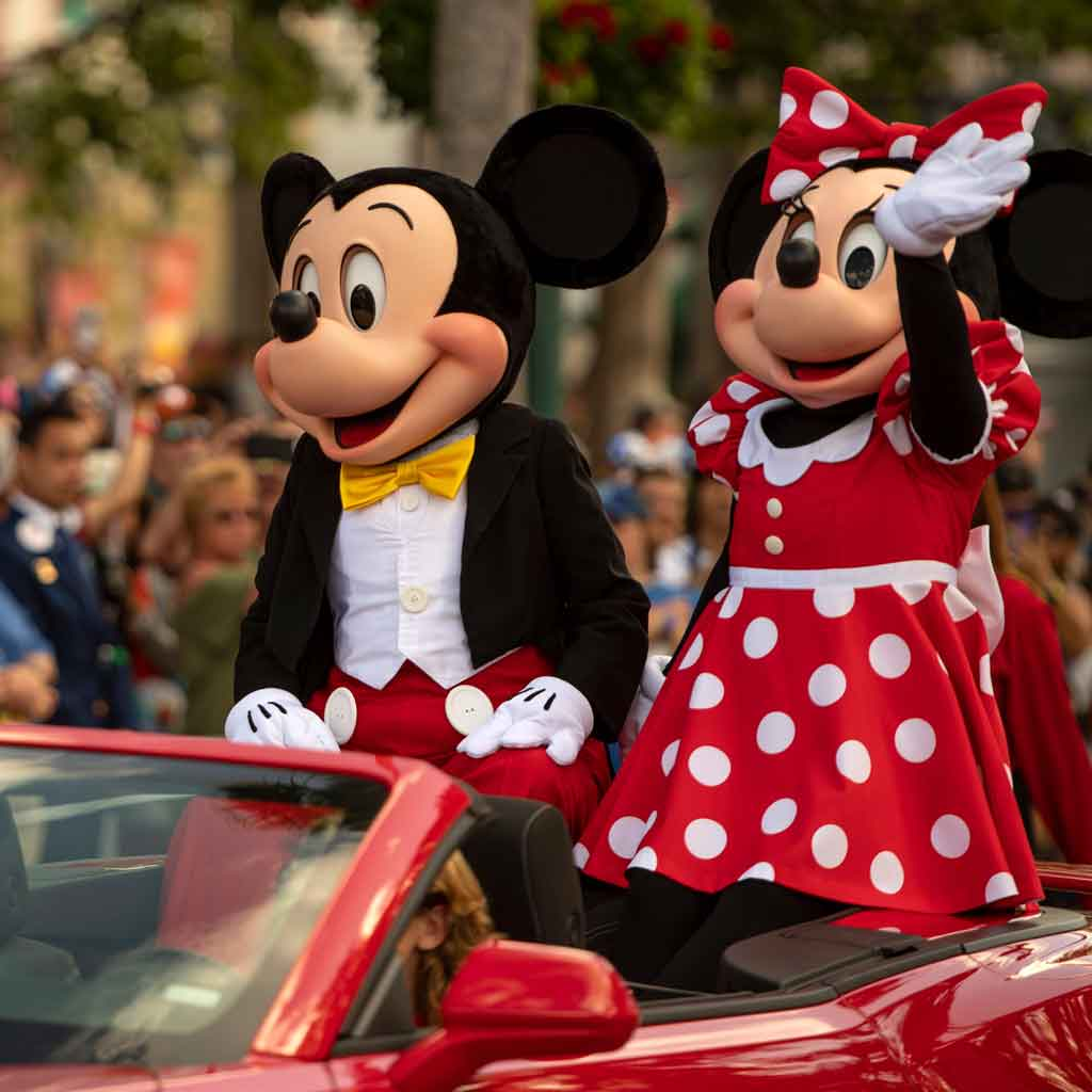 Mickey and Minnie Mouse sitting on the back of a red convertible car, waving at guests.