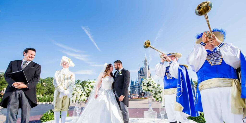 A bride and groom looking at each other while 2 trumpeteers in Renaissance garb play their horns.