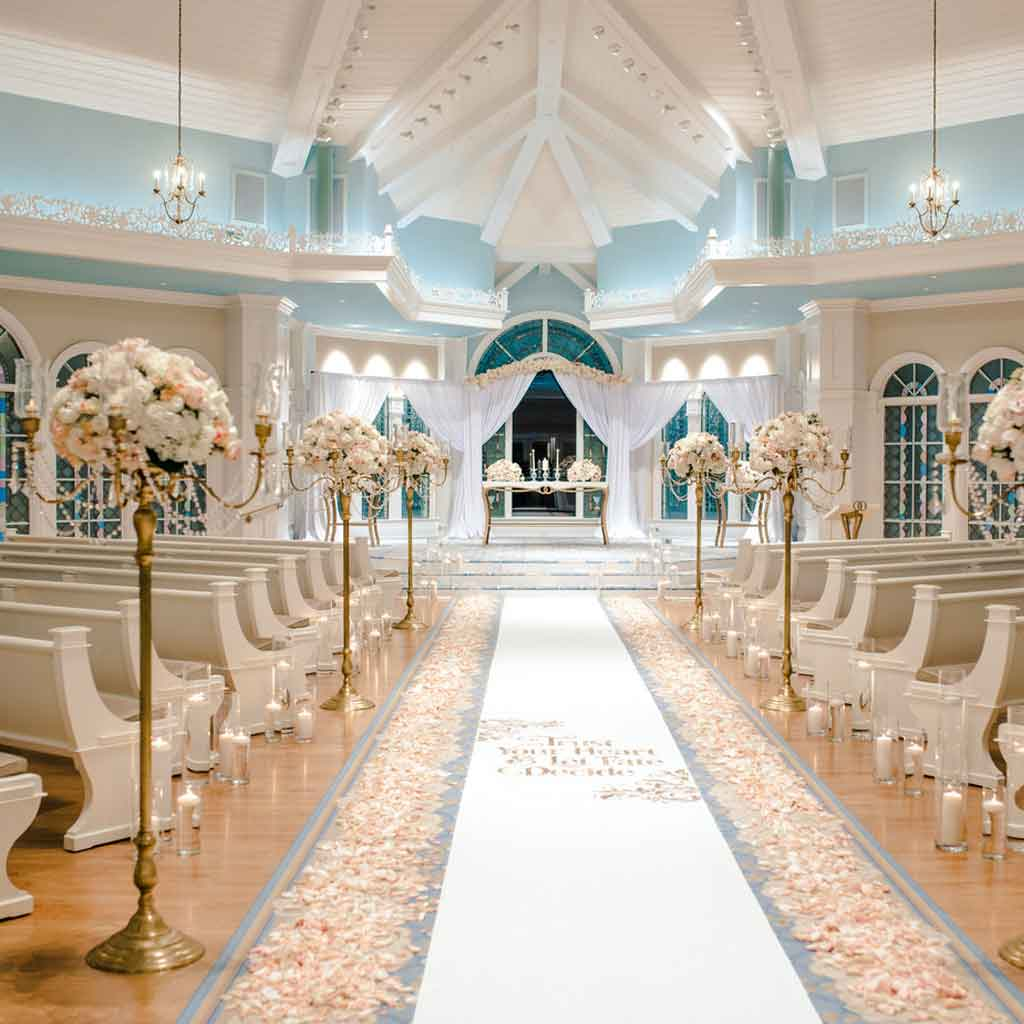 A wedding ceremony venue with white floral displays, candles, and a runner lined with flower petals.