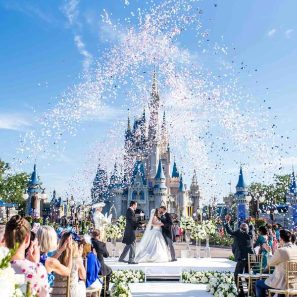 A bride and groom kiss while a crowd cheers and confetti flies in the air.