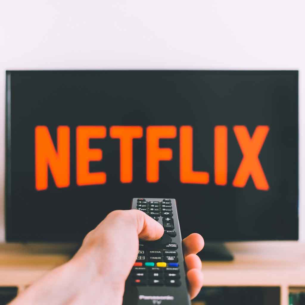 Closeup of a hand holding a remote pointing at a TV with the Netflix logo.