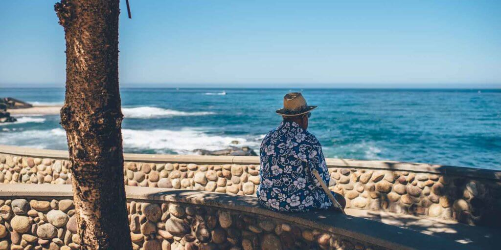 Man wearing a Hawaiian shirt sitting on a stone wall while looking out to the ocean.