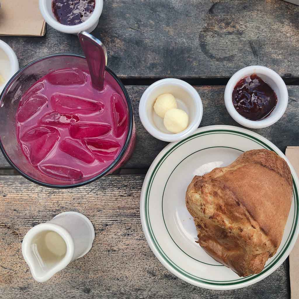 Flat lay photograph of blueberry lemonade and a popover against a wooden table.