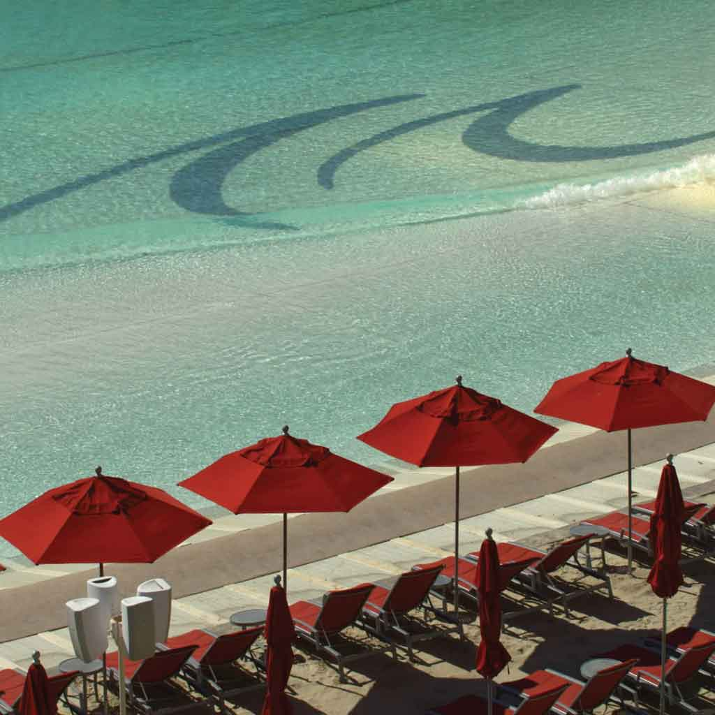 Closeup of an artificial beach with red lounge chairs and umbrellas on the side.