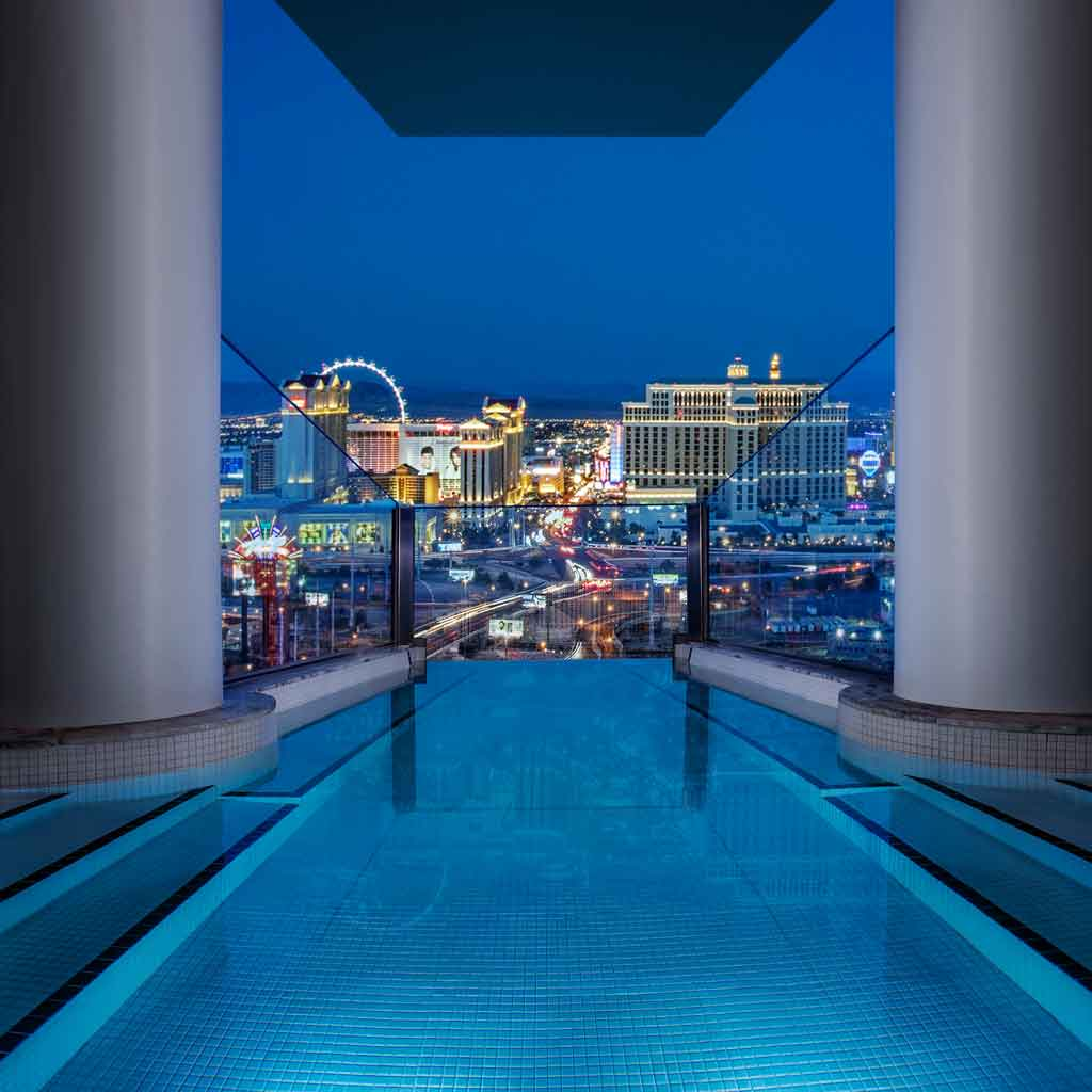 Closeup of an infinity pool looking out over Las Vegas at night.