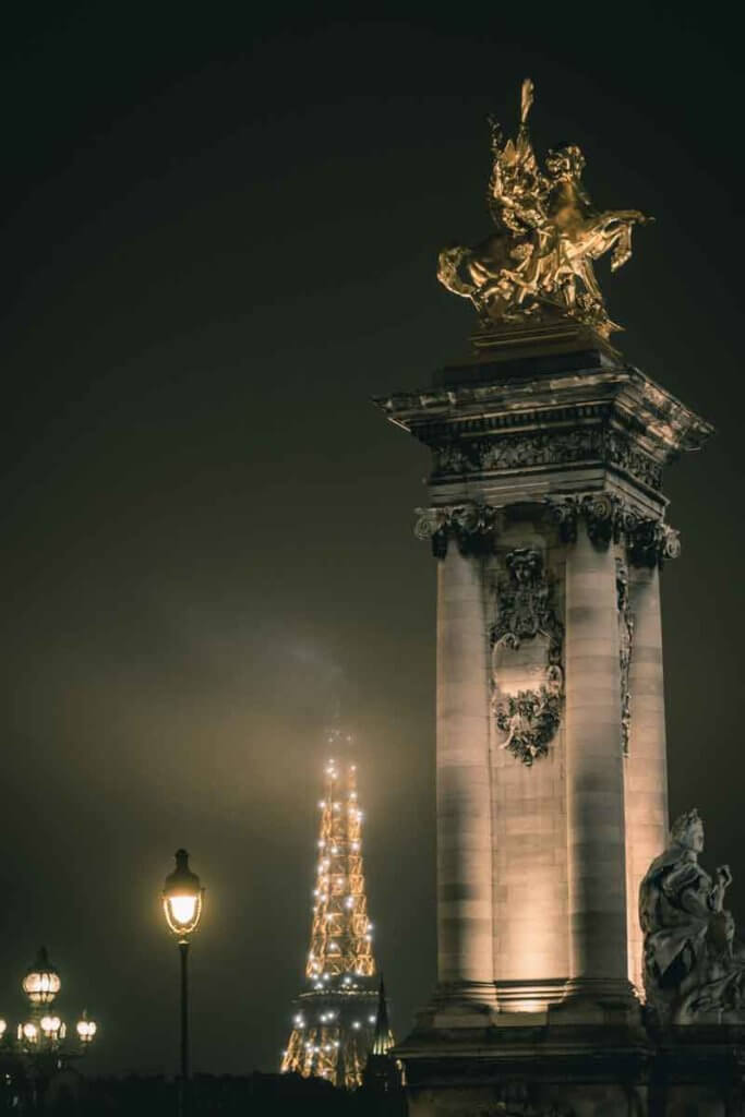 Nighttime photo of a a statue in Paris, France with the Eiffel Tower in the background and lots of fog.