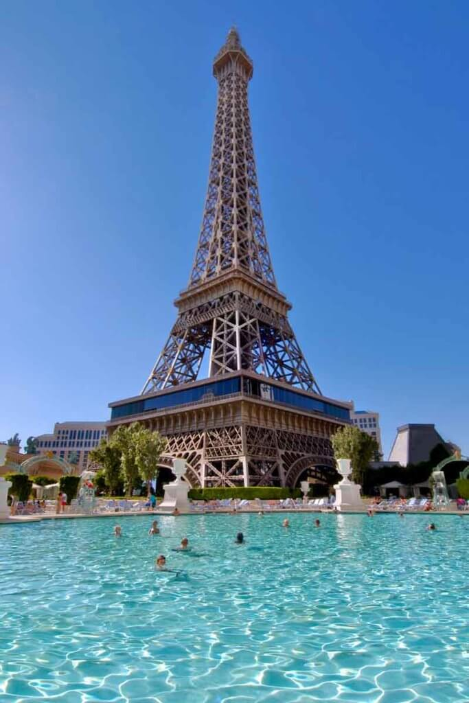 A pool with people in it beneath a replica of the Eiffel Tower.