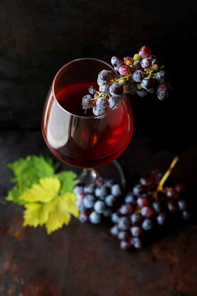 Closeup of a glass of red wine with several bunches of grapes.