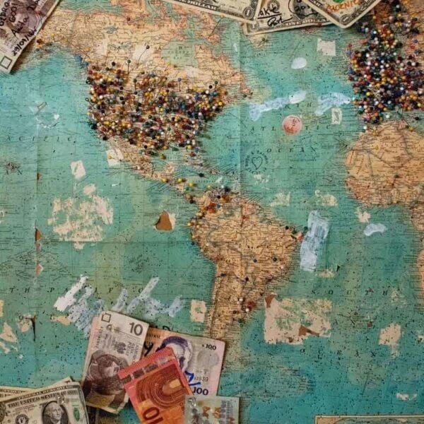 A map hung up on corkboard with lots of pins in different locations and currency from around the world attached.