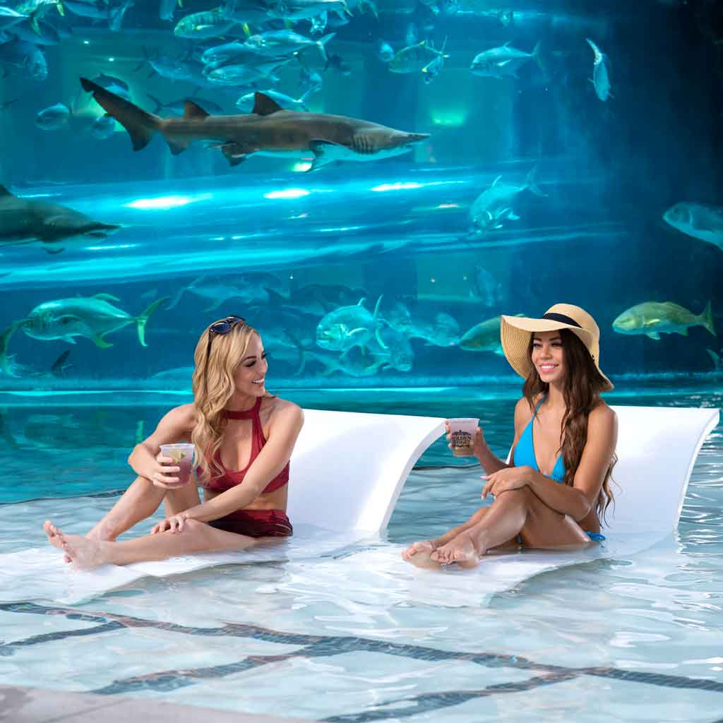 Two women on lounge chairs set inside a pool in front of an aquarium with sharks and fish.