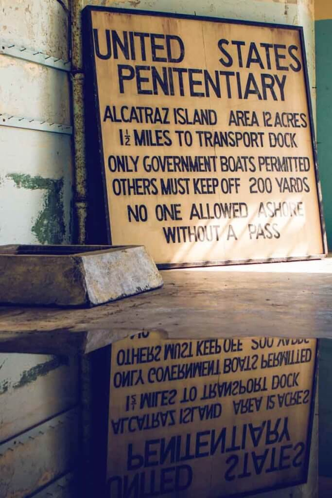 """Closeup photo of a sign that says """"United States Penitentiary. Alcatraz Island. Area 12 acres. 1.5 miles to transport dock. Only government boats permitted. Others must keep off 200 yards. No one allowed ashore without a pass."""""""