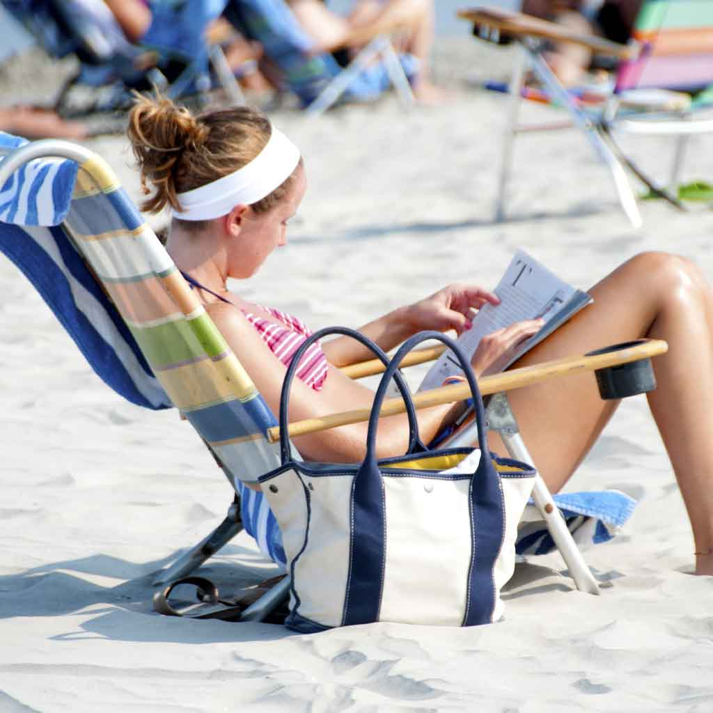 Woman sitting in a beach chair on a sandy beach while reading a magazine.