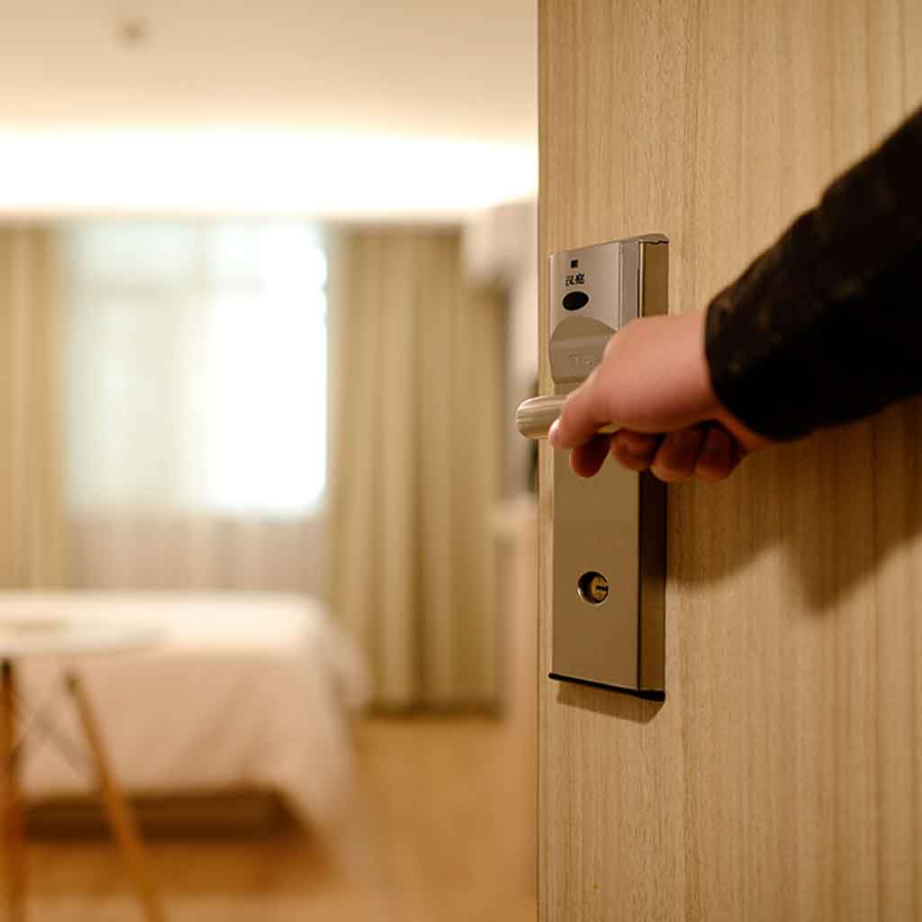 Closeup of a person opening a door to a hotel room.