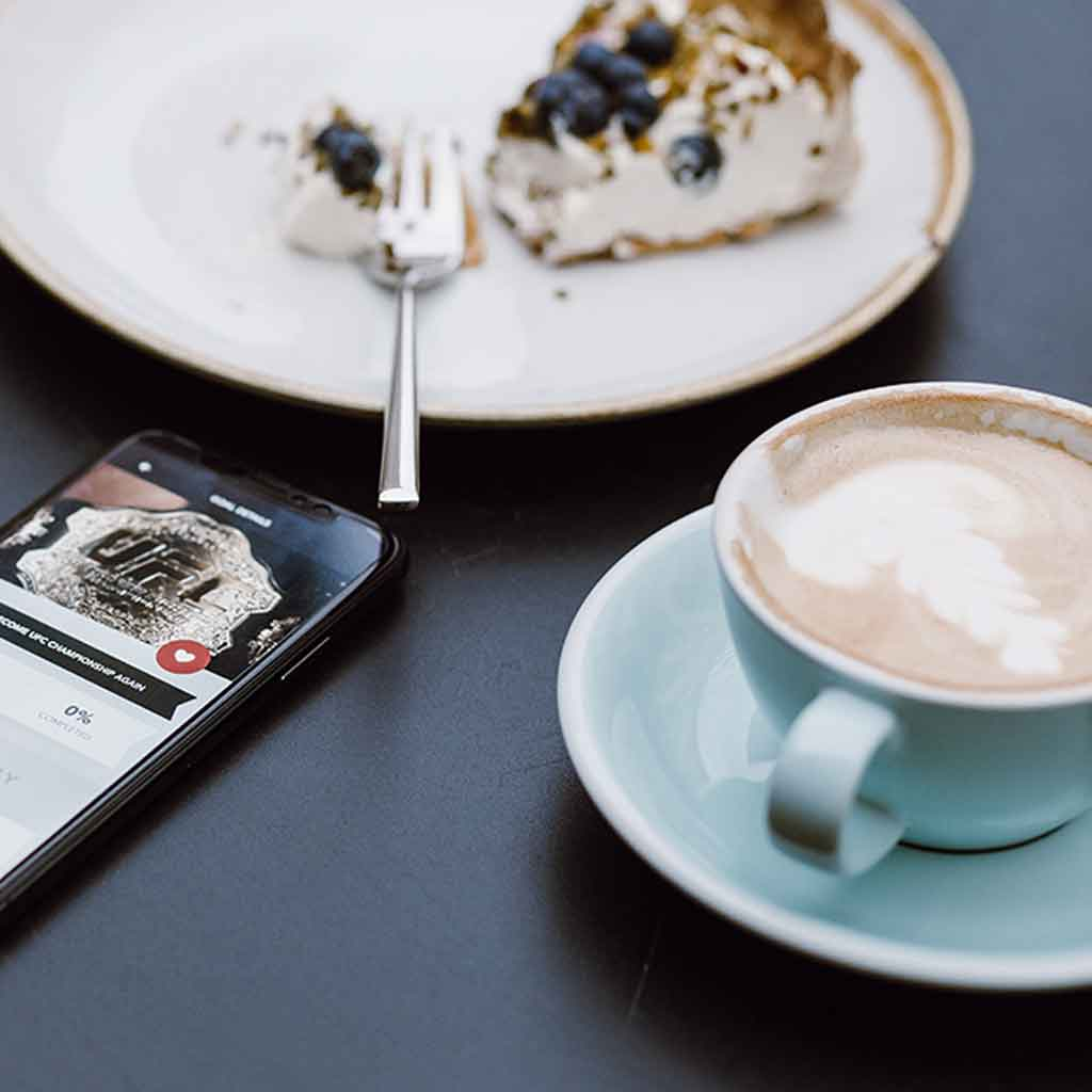 Closeup of a smartphone, plate with a half eaten piece of pie, and a cup filled with a latte.