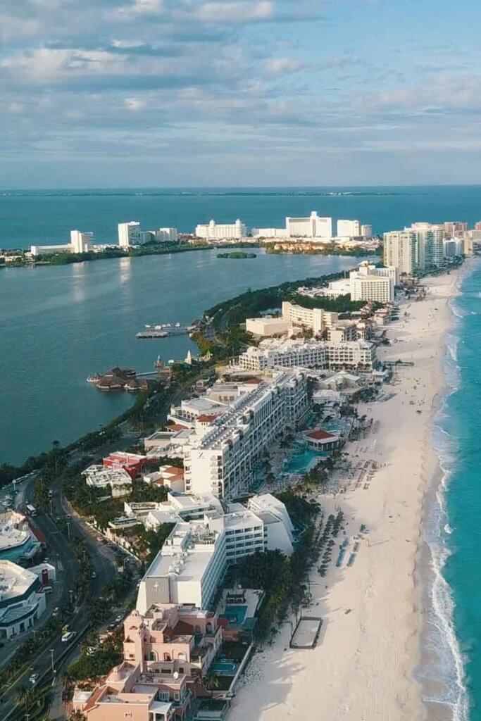 Aerial view of a long stretch of beach with many tall and large buildings down the coast.