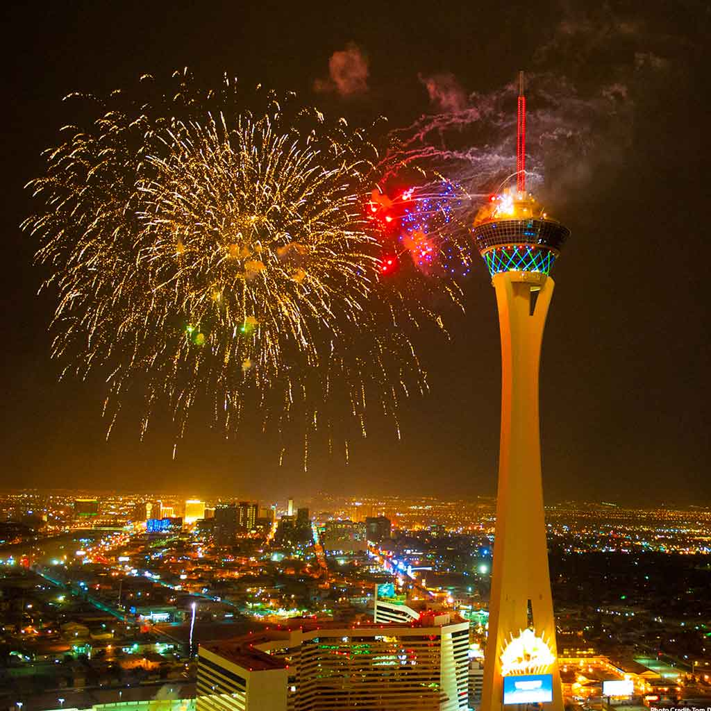 A tall observatory tower set against a city skyline with fireworks bursting.
