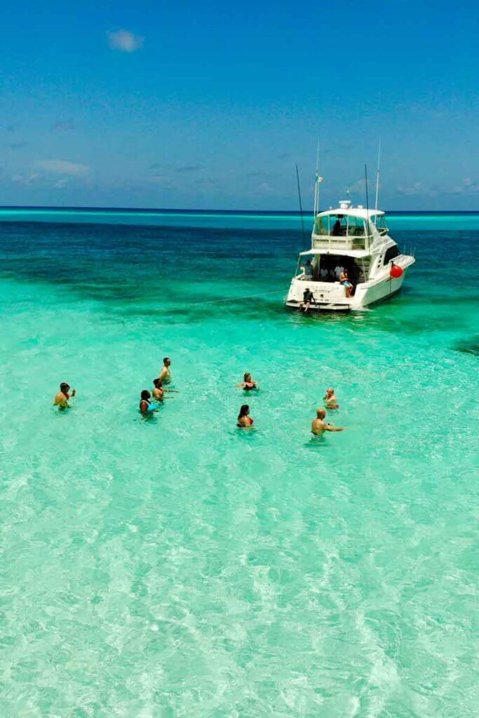 People standing in a turquoise ocean with a boat nearby.