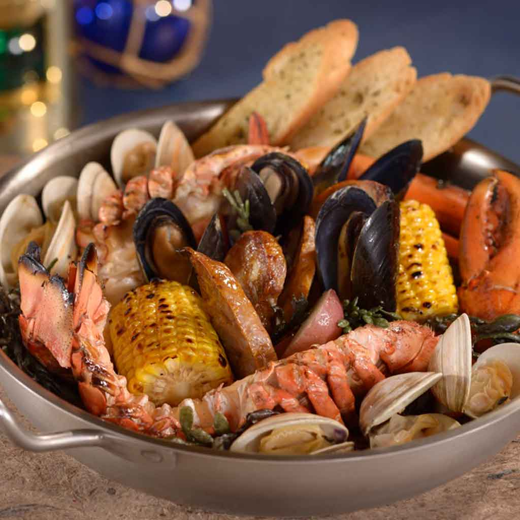 Closeup of a seafood boil plate with lobster, mussels, corn on the cob, and more.