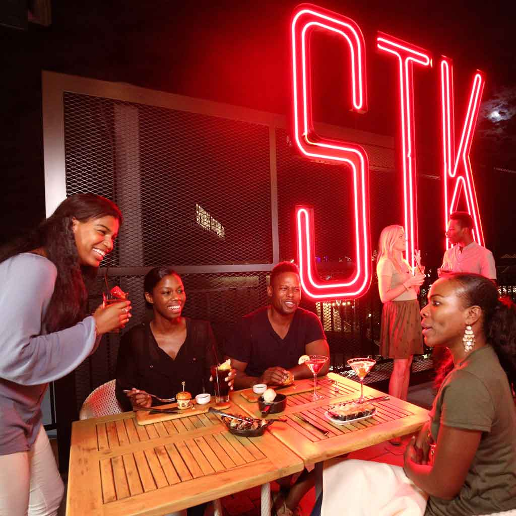 Landscape photo of a group of 4 friends at STK restaurant.