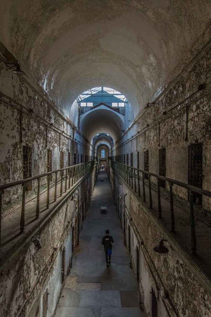 Aerial view of an abandoned prison with a person walking down the hallway.
