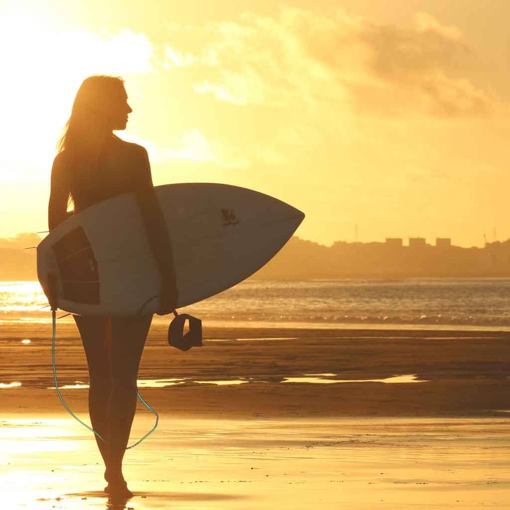 Silhouette of a woman carrying a surfboard with the sun shining on her.