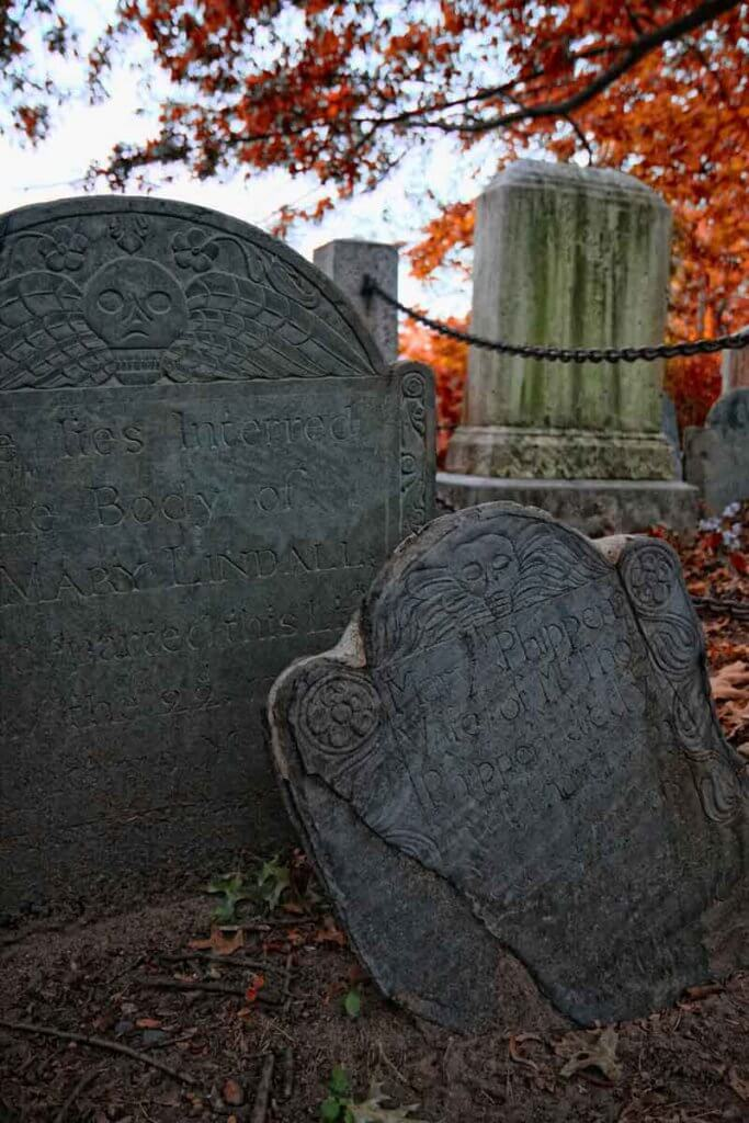 Closeup of 2 old gravestones amidst red fallen leaves.