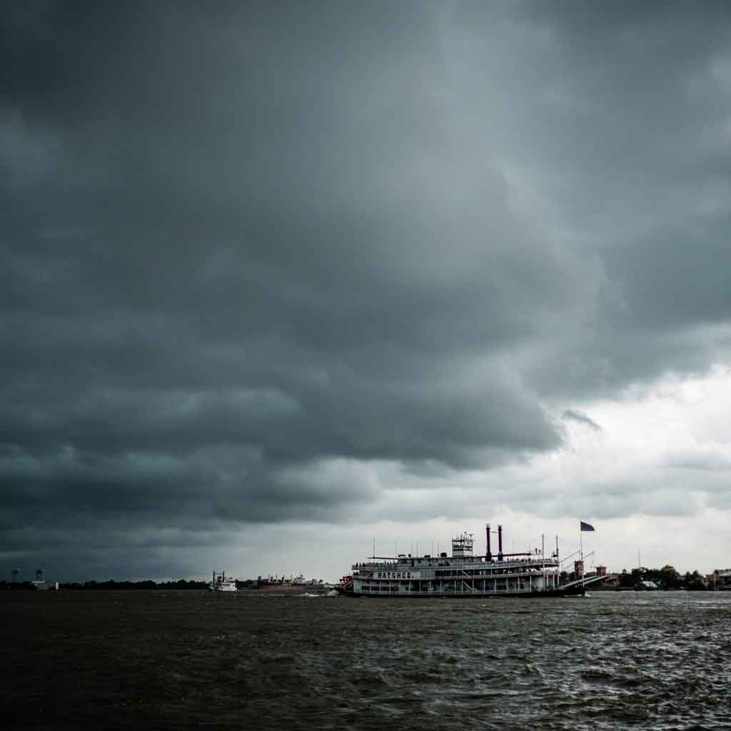 Photo of the Natchez steamboat on the Mississippi River in gray, stormy weather.