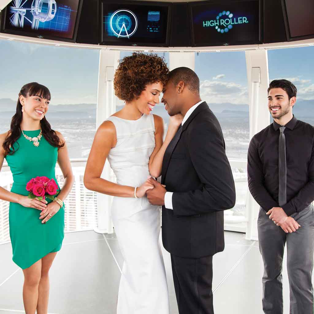 "Photo of a bride and groom canoodling while two people look on. A sign in the background says ""High Roller."""