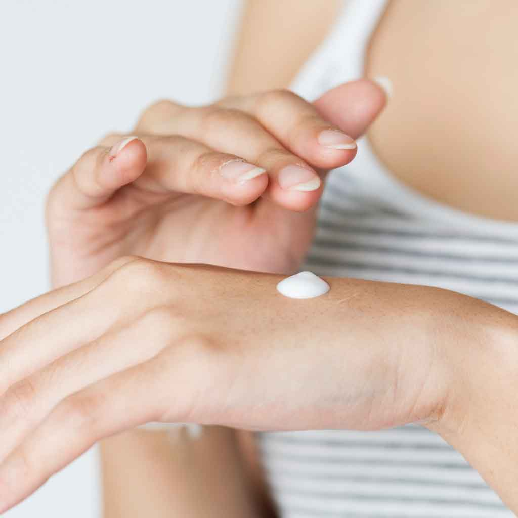 Closeup of a woman about to rub a drop of sunscreen on her hand.