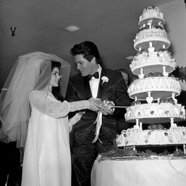 Historical photography of Elvis and Priscilla Presley on their wedding day, cutting a 6-tier weddingcake.