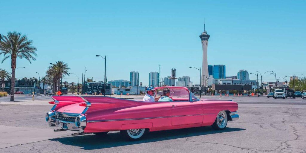 Two men riding in a pink Cadillac convertible in a city.