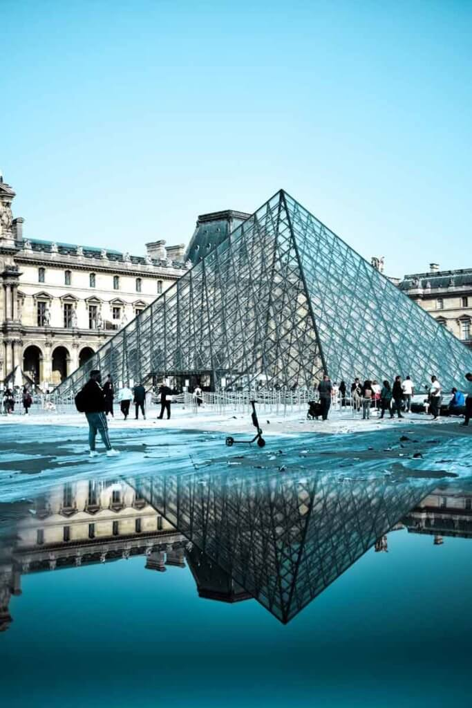 Closeup view of the iconic glass pyramid at the Louvre, reflecting in a puddle of water.