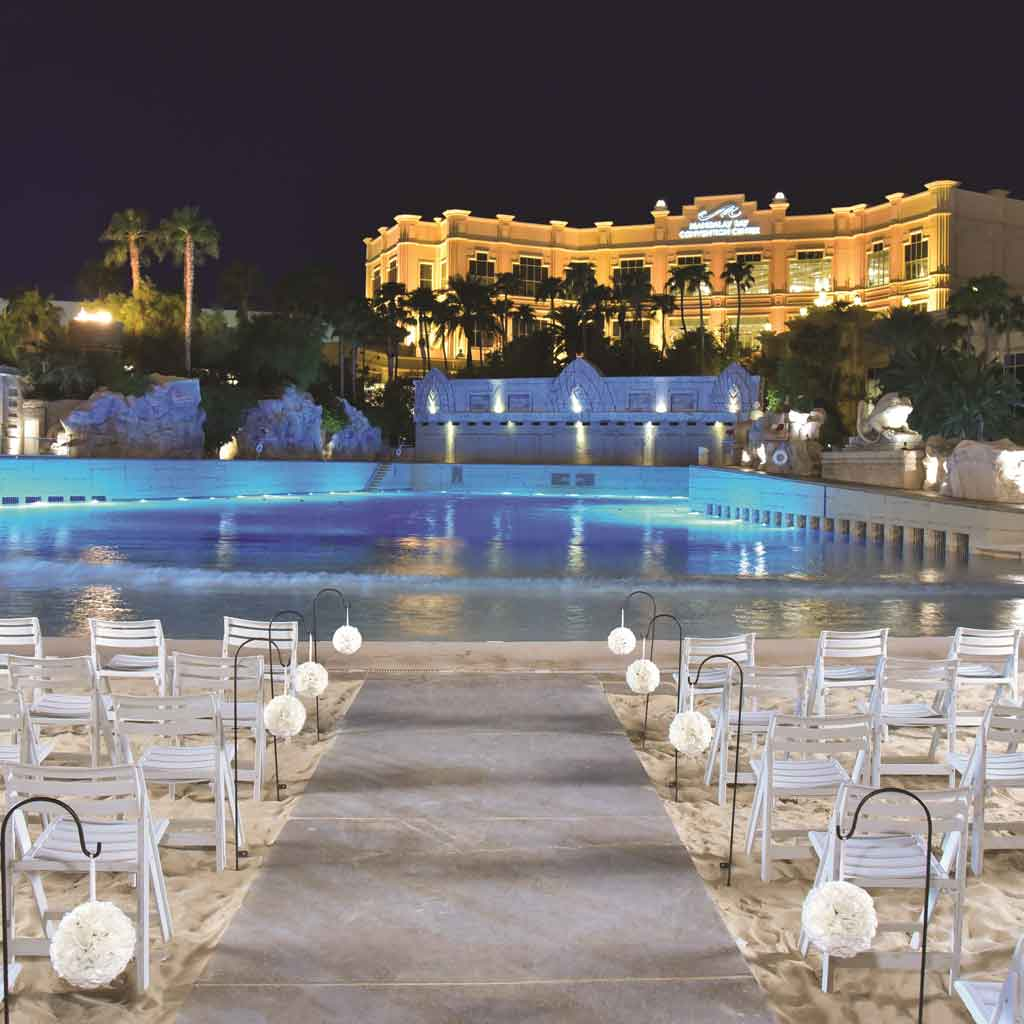Landscape view of a wedding ceremony set up on a faux sand beach in front of a pool with a hotel in the background.
