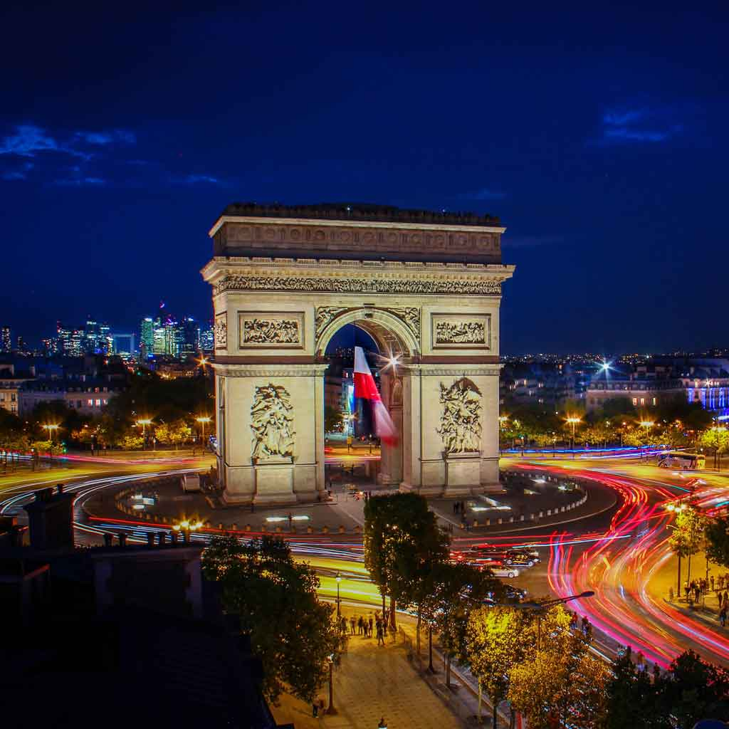 Aerial view of the Arc de Triomphe at night with the flag of France hanging in the middle.