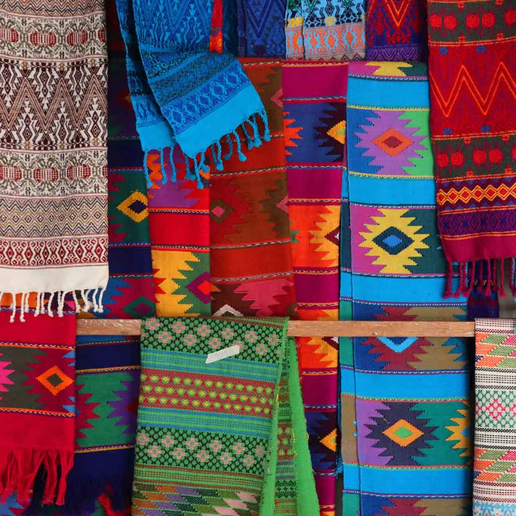Closeup view of brightly colored textiles with traditional Mexican and Mayan prints.