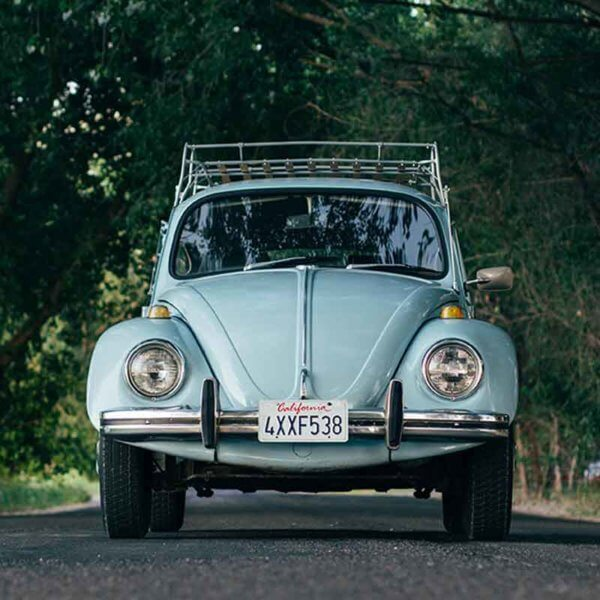 Landscape view of a vintage blue Volkswagon Beetle car parked in the middle of a street with lots of trees shading it.