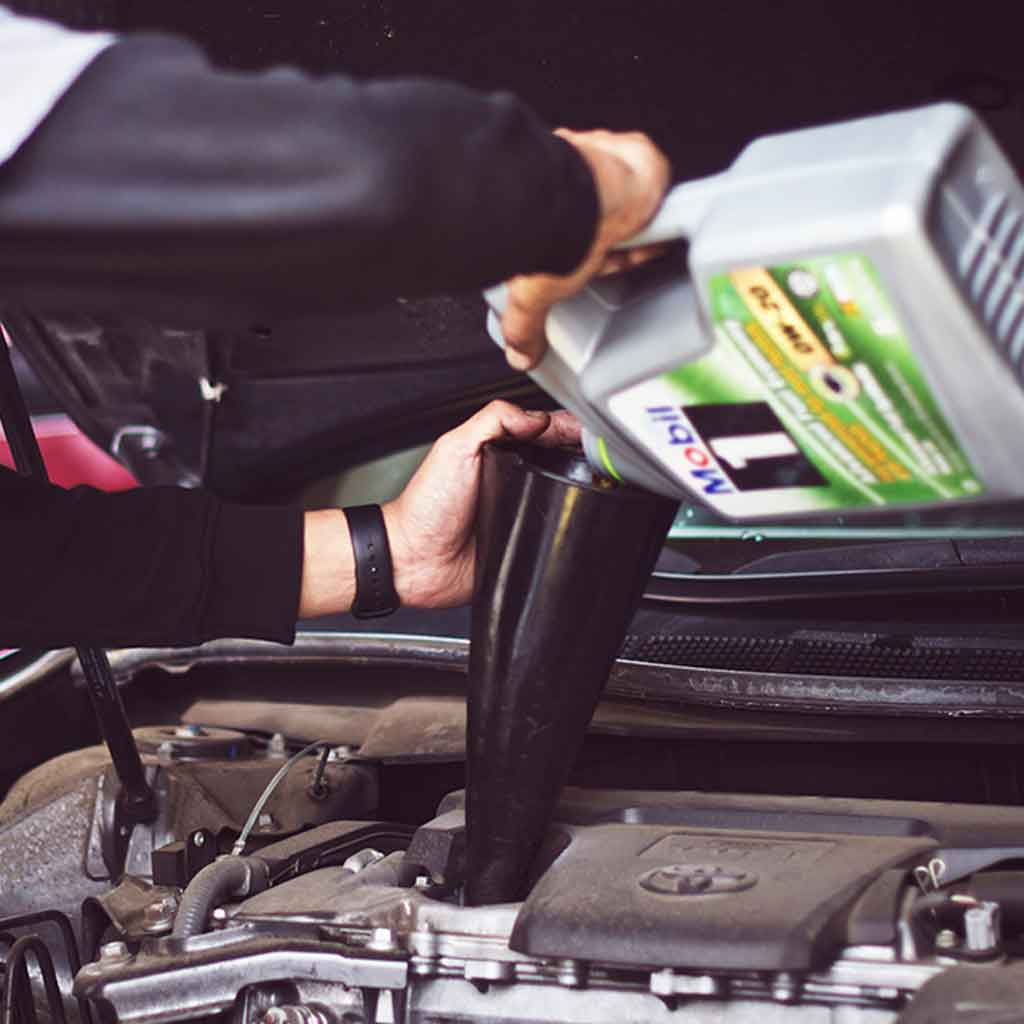 Closeup of a person pouring motor oil into a funnel over a car engine.