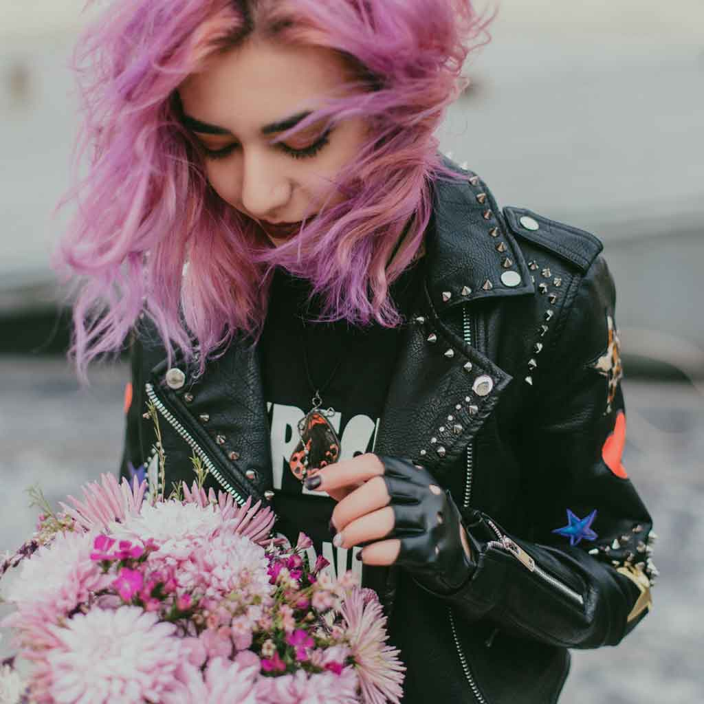 Closeup of a woman with lavender hair wearing a leather jacket and carrying a floral bouquet.