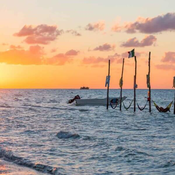 Landscape view of a beach at sunset with hammocks set up in the water.