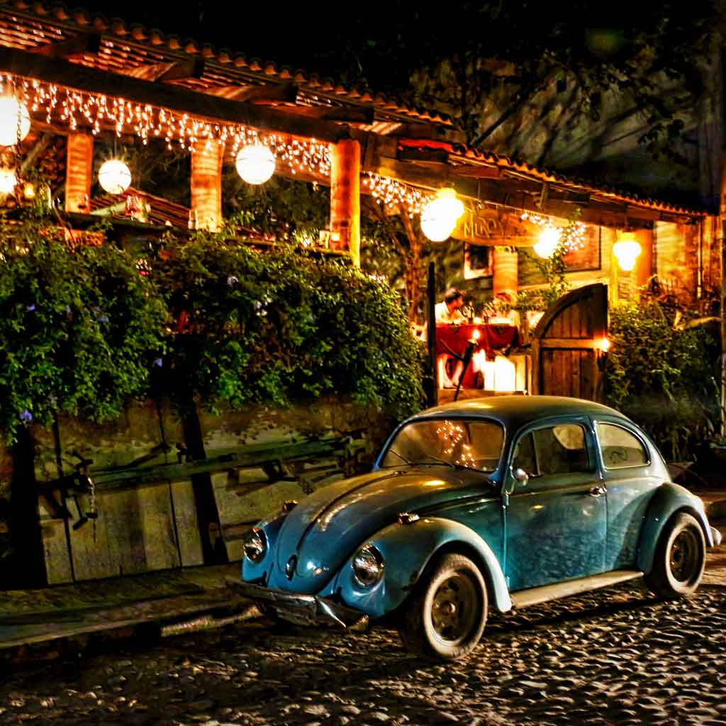 Landscape view of a cobblestone street with a vintage blue Volkswagon beetle parked outside a festive building at night.