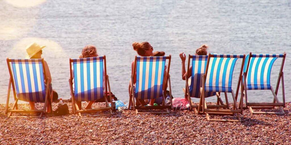 Photograph of striped beach chairs with a few women sitting on them set on sand overlooking the ocean.