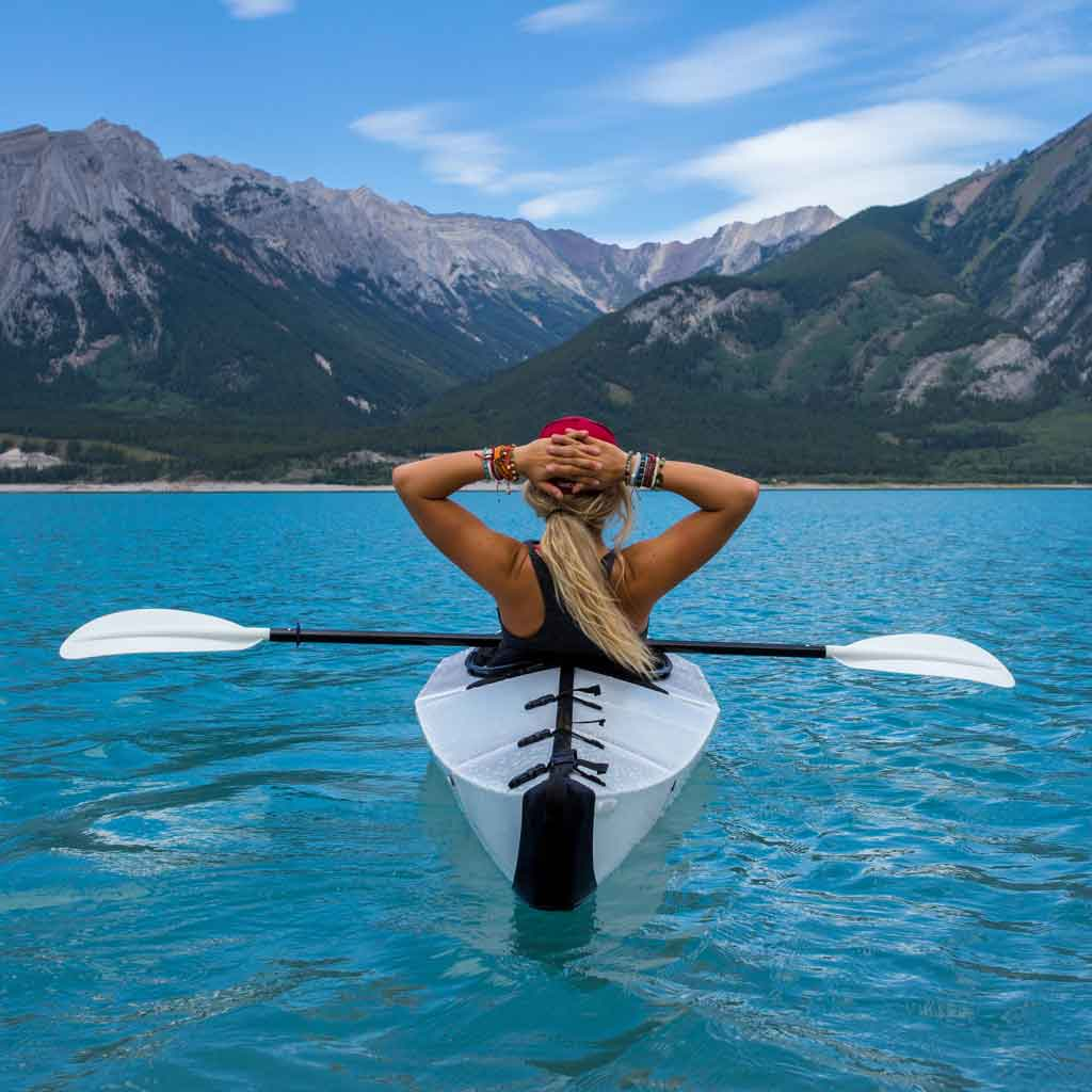 Photograph of a woman in a white kayak on turquoise waters resting with her hands on the back of her head looking out to mountains in the distance.
