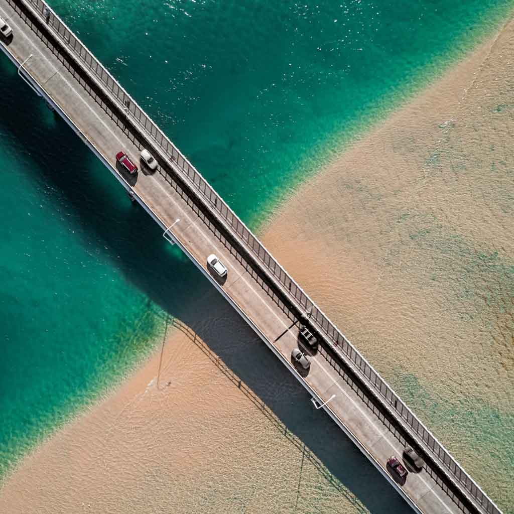 Aerial view of cars driving over a highway over turquoise water and sand.