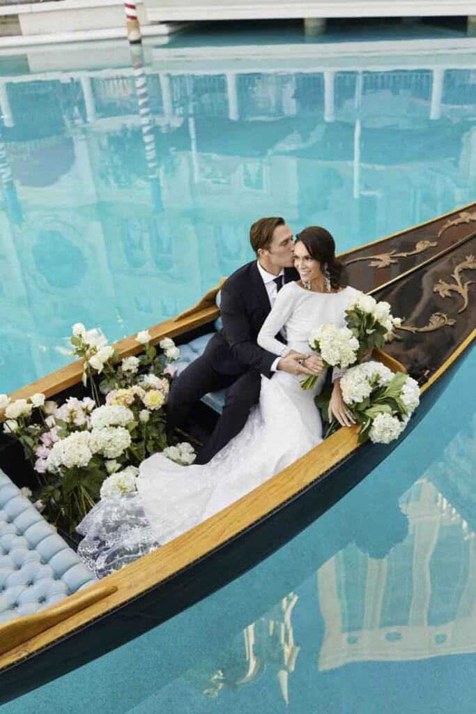 Closeup of a bride and groom posing in a gondola.
