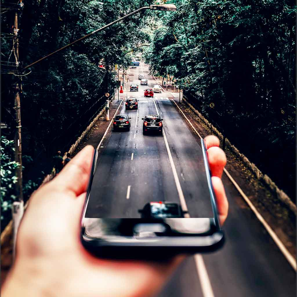 Photo collage of a person holding a phone perpendicular to a road so that it looks like cars are driving out of it onto the road.