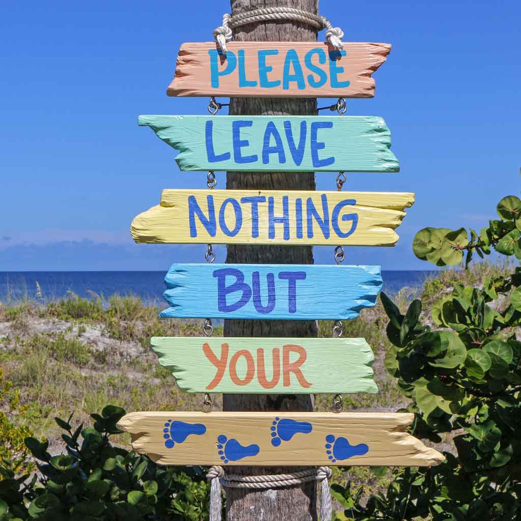 "Closeup of a wooden sign that says ""Please leave nothing but your...[4 silhouettes of footprints]"""