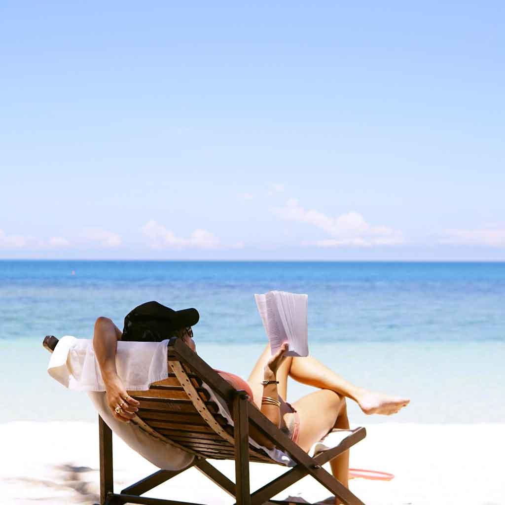 View of a woman from behind in a lounge chair reading a book while sitting on the beach.
