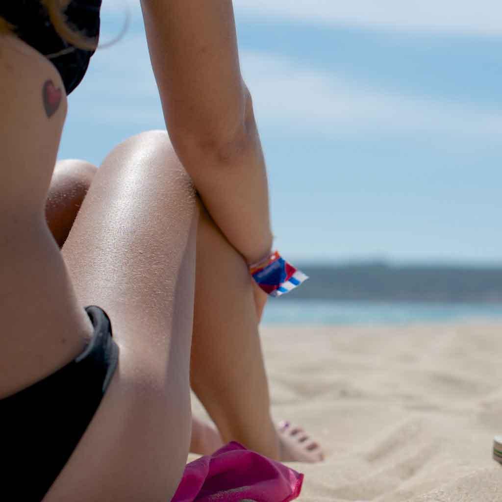 Closeup of the side of a woman in a bikini sitting on a beach.
