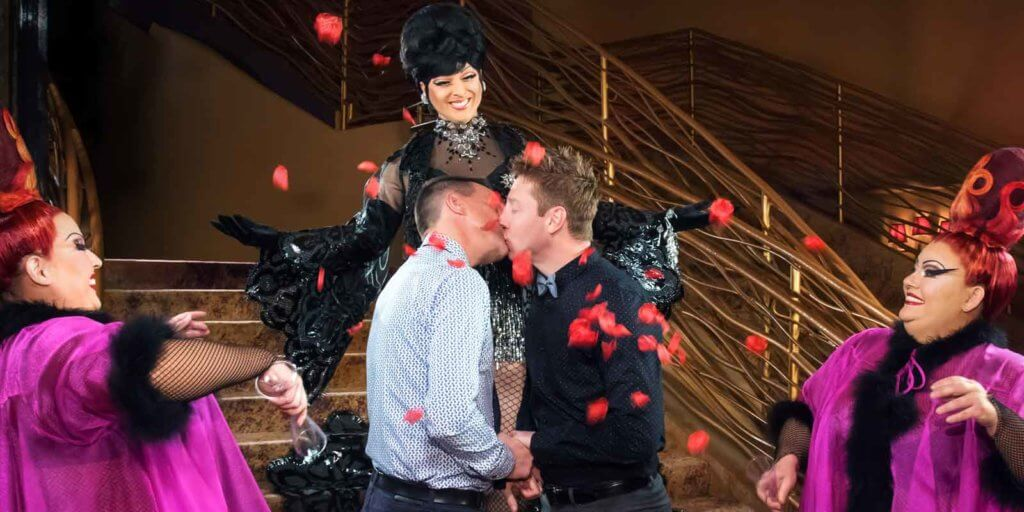 Photograph of a male couple kissing while dramatically dressed show performers look on lovingly.